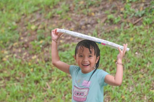 雨の日に笑顔の顔を笑って遊んでアジア少女