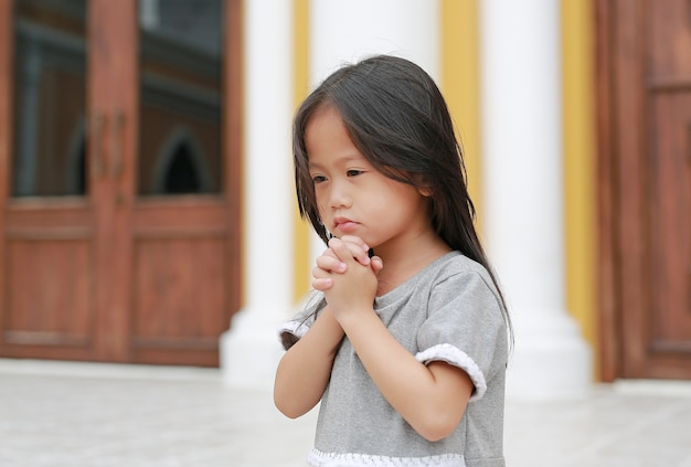 Little asian child girl praying in front of the church.