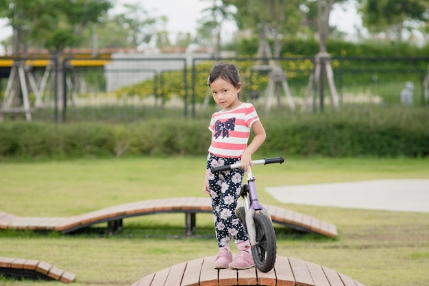 Little asian child girl ride bike at playground