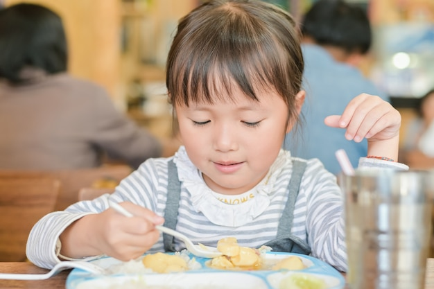 Little asian child girl use spoon to scoop food on the table to dine. while having lunch on table in restaurant