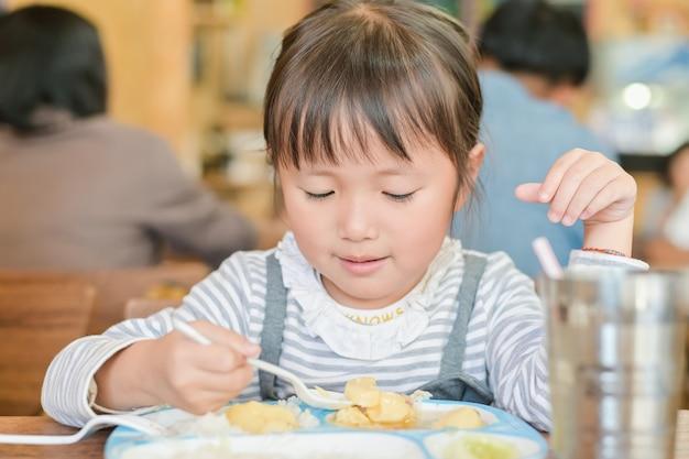 アジアの子少女は、スプーンを使用してテーブルの上に食べ物をすくって食事をします。レストランのテーブルで昼食をとりながら
