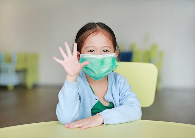 Little asian child girl wearing a protective mask with showing five fingers