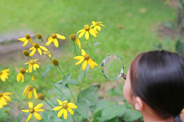 Little asian child girl with magnifying glass on green grass garden.