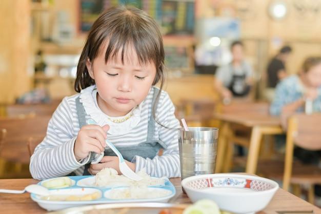 レストランのテーブルで昼食を食べている間不幸な顔を持つ小さなアジアの子女の子、つまらない食べる人は食べたくないまたは空腹ではない