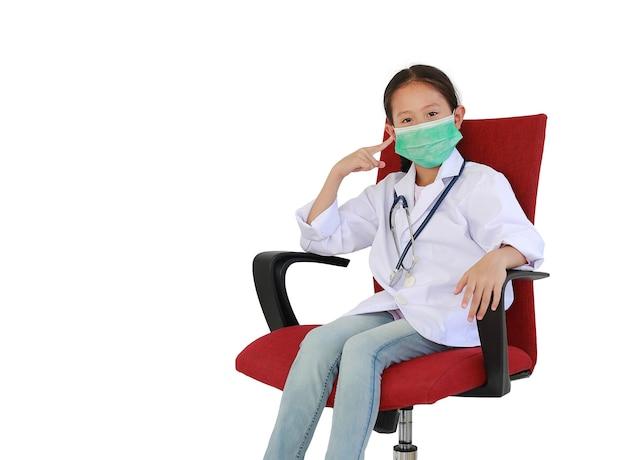 白い背景で隔離の椅子に座っている医療マスクに人差し指を指すドクターガウンの小さなアジアの子供。クリッピングパスとコピースペースのある画像