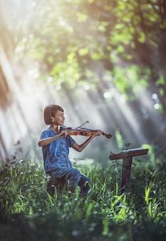 야외에서 바이올린을 연주 작은 아시아 아이