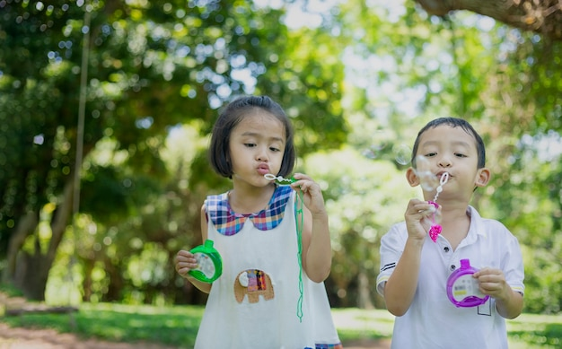Little asian children blowing bubbles, playing with joy and happiness in the beautiful and green nature.