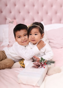 Little asian children boy and a woman in sweaters opengifts and play while sitting on the bed at home