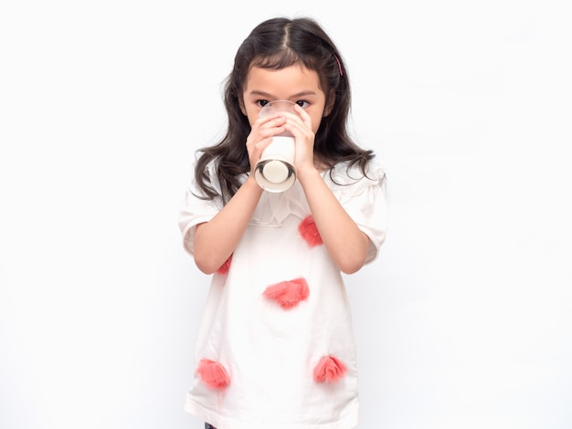 Little asian cute girl 6 years old holding and drinking milk from glasses
