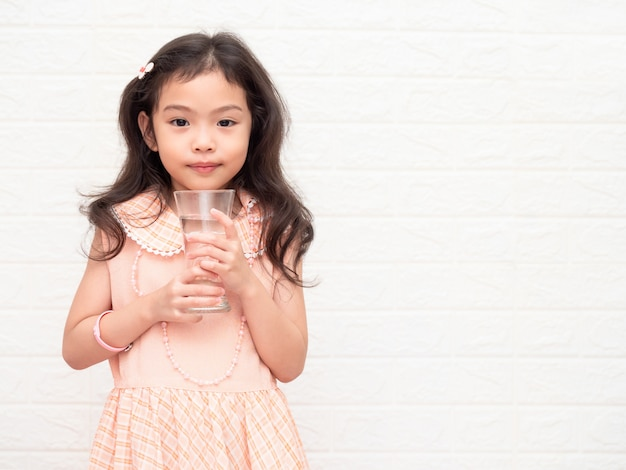 Little asian cute girl 6 years old holding and drinking water from glasses.