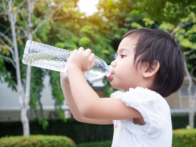 Little asian cute girl years old drinking water from plastic bottle.