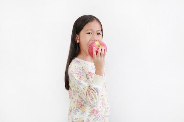 Little asian girl biting red apple on white