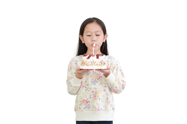 Little asian girl blowing candle on happy birthday cake isolated