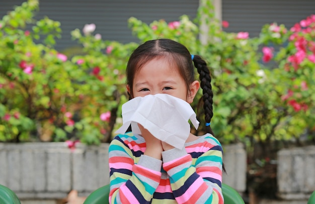 Little asian girl blowing her nose with tissue paper sitting outdoor.