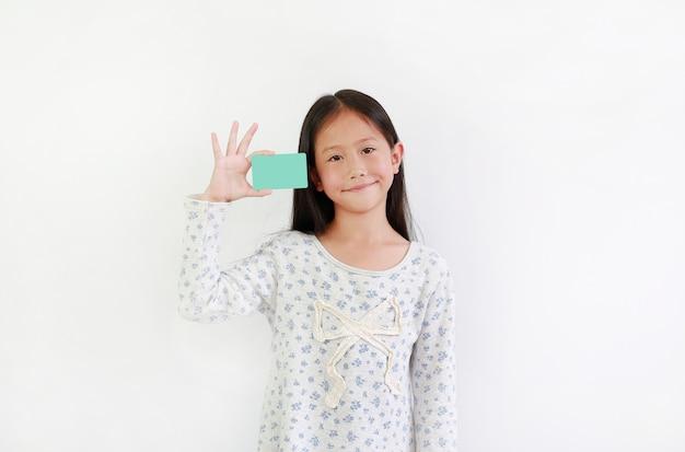 Маленькая азиатская девочка, показывающая пустую голубую карту на белом фоне
