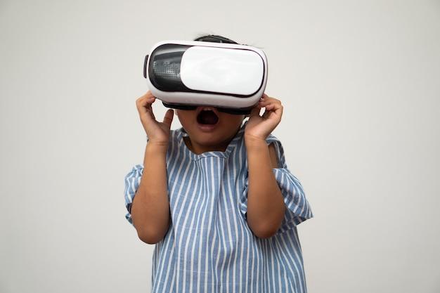 Маленькая азиатская девочка с гарнитурой виртуальной реальности увлекательна для новых впечатлений.
