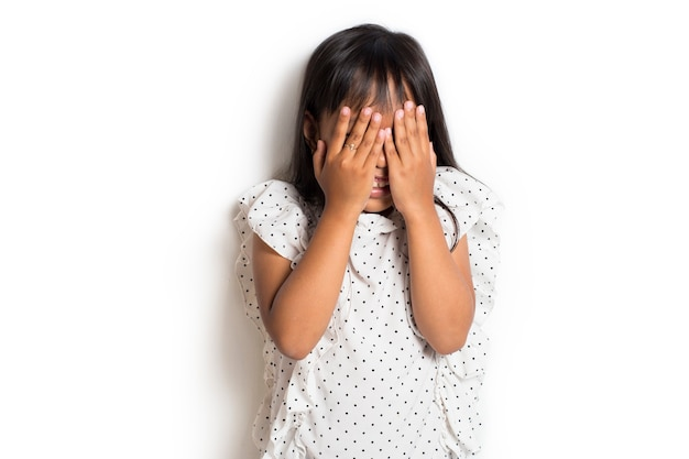 Little asian girl covering face with hands