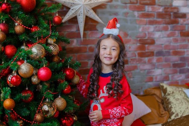 Маленькая азиатская девочка украшает елку, улыбаясь рождество, новый год