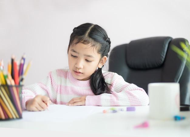 教育コンセプトの宿題をしている小さなアジアの女の子