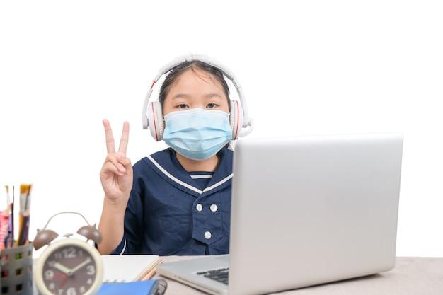 ノートパソコンで宿題をしている小さなアジアの女の子