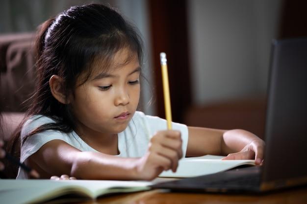 オンラインレッスンをしている小さなアジアの女の子