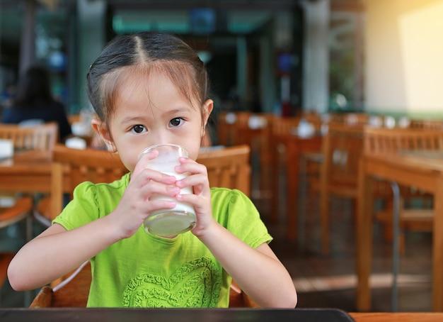 朝のレストランで牛乳を飲む少年。