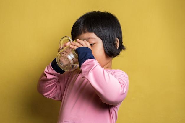 유리에서 작은 아시아 소녀 식 수