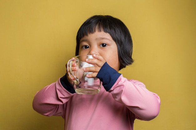 Маленькая азиатская девушка пьет воду из стекла