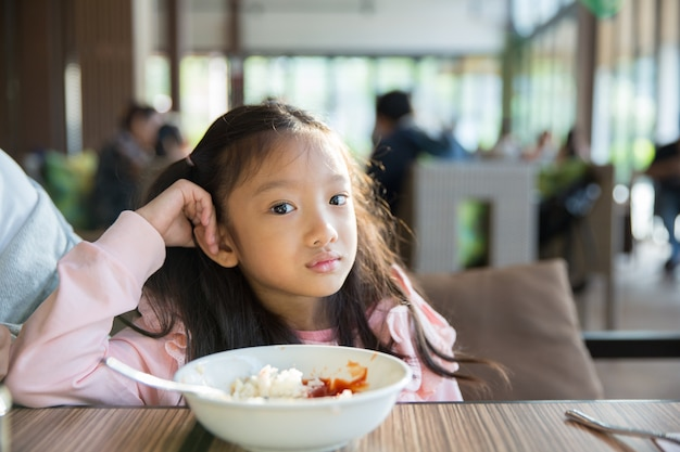 Little asian girl feeling bore the food with the rice and tomato sauce