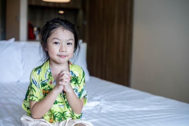 小さなアジアの女の子の手で祈る、信仰、精神性、宗教のための祈りの概念で折りたたまれた手。