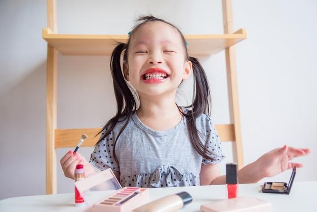 혼자서 화장품으로 그녀의 얼굴을 화장하는 동안 작은 아시아 소녀 재미