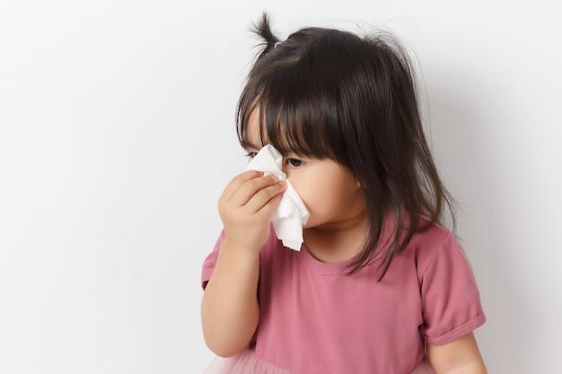 Маленькая азиатская девушка держа ткань и дует ее нос. малыш с холодным насморком.