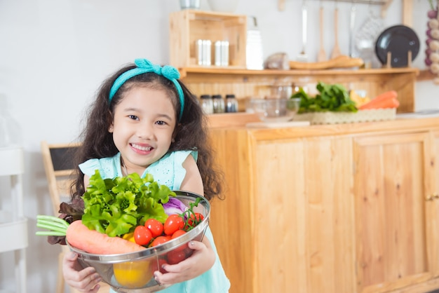 Little asian girl holding basket with many vegetables and smiles in kitchen