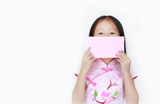 Little asian girl holding chinese new year pink envelope packet on her mouth.