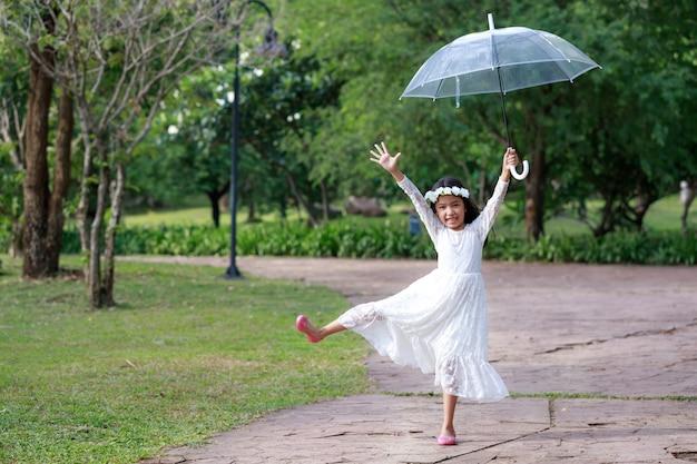 明確な傘を押しながら幸せに笑みを浮かべて小さなアジアの女の子