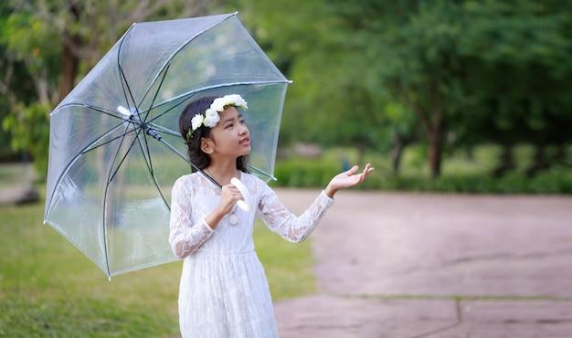 明確な傘を押しながら笑顔の小さなアジアの女の子