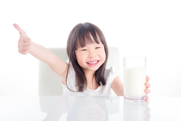 Little asian girl holding a glass of milk and showing thumb up over white background