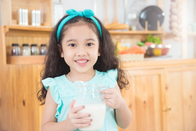 Little asian girl holding a jug of milk and smiles in the kitchen