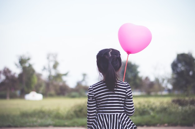Little asian girl holding pink balloon in hand