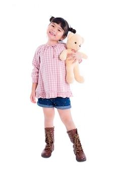 Little asian girl holding teddy bear and smiles over white background