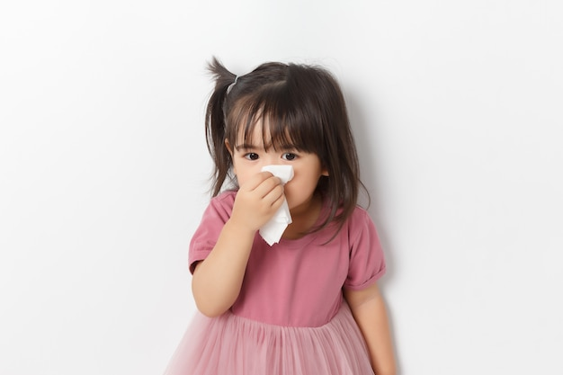 Little asian girl holding a tissue and blow her nose. kid with cold rhinitis.