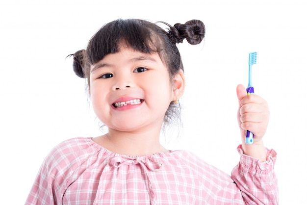 Little asian girl holding toothbrush and smiles over white background