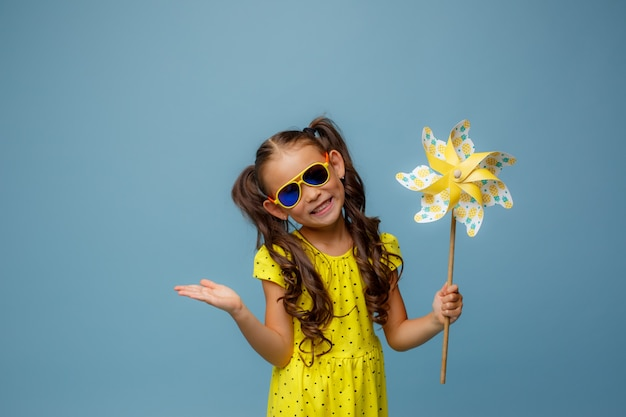 Little asian girl holding a toy windmill, smiling, studio on blue