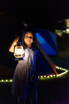 Little asian girl holding a vintage lantern while camping in dark night