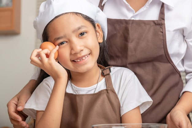 The little asian girl holds the egg in her hand