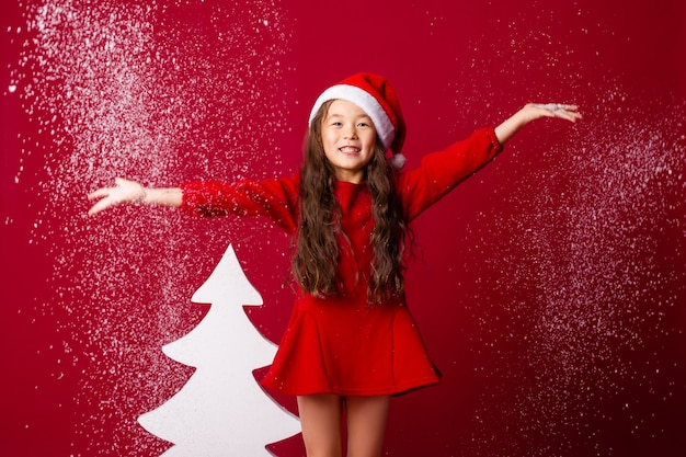 サンタの帽子をかぶった小さなアジアの女の子が彼女の手のひらから雪を吹き飛ばすクリスマスコンセプトテキストスペース