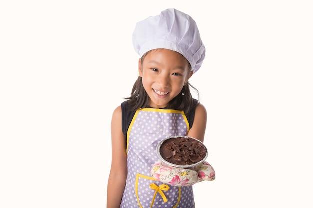 シェフのドレスを着た泡立て器でチョコレートベーカリーケーキを作って楽しむ小さなアジアの女の子
