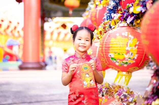 Маленькая азиатская девушка в китайском традиционном платье держит красный конверт. счастливый китайский новый год концепция.