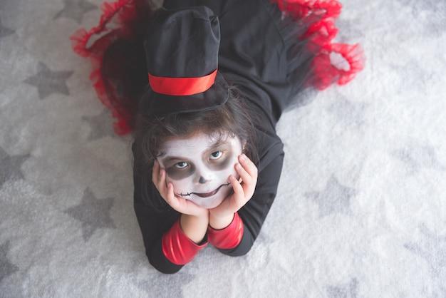 床に横たわっているハロウィーンの衣装のリトルアジアの女の子