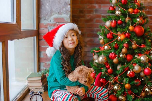 Маленькая азиатская девушка в пижаме сидит на окне возле елки с медведем рождество новый год